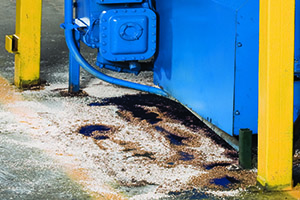 oil dry kitty litter soaking up oil at a manufacturing plant