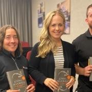 ITU Absorbtech book club participants hold up a John C. Maxwell book