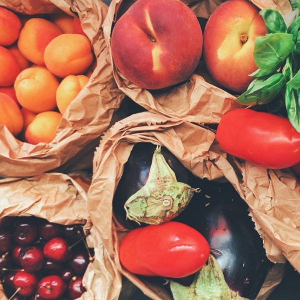 farm fresh eggplant, peaches, cherries in brown paper bags