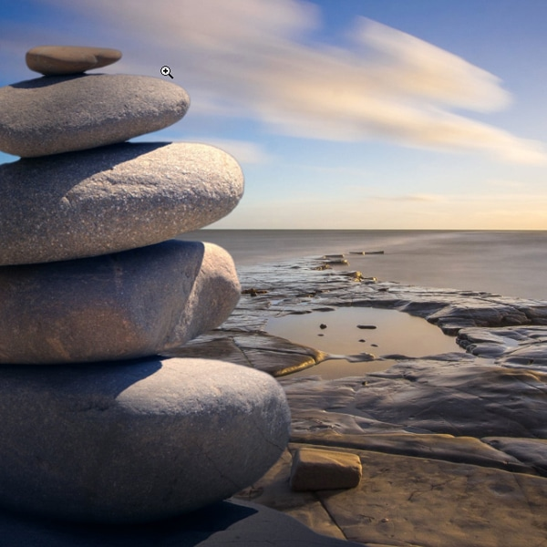 peace stones stacked up by the water